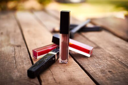 Liquid Lipstick cosmetic on wood table on nature background