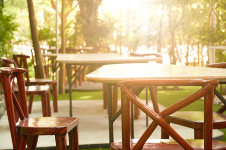 The restaurant table in a restaurant style restaurant and shady garden with trees around it copy space table with tree green garden flare light