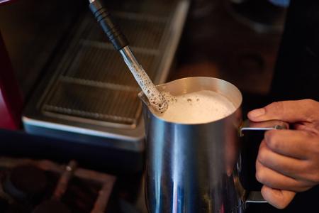Barista Barrister makes coffees in coffee bar.latte preparation in coffee machine.Hands bartender cooking coffee, steam milk preparation milk for latte coffee shallow depth of field. 写真素材