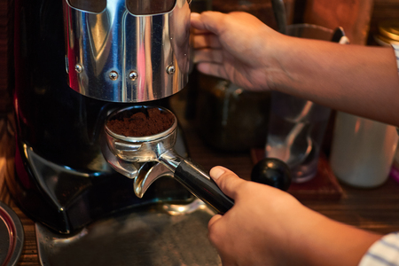 Barista makes coffees in coffee bar.espresso preparation in coffee machine.Prepare espresso coffee maker with fresh coffee. Hands bartender cooking coffee in the coffee machine, Interior bar, bartender, shallow depth of field.Coffee grinder 写真素材