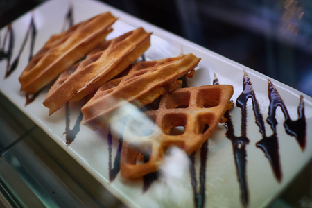 Pieces of waffle on white plate topped with chocolate on top of the cabinet sweets.