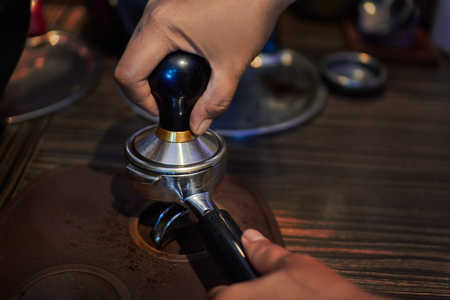 Barista makes coffees in coffee bar.espresso preparation in coffee machine.Prepare espresso coffee maker with fresh coffee. Hands bartender cooking coffee in the coffee machine, Interior bar, bartender, shallow depth of field.Coffee grinder 스톡 콘텐츠