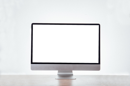 Computer display with blank white screen. Front view. on office table on white background Foto de archivo