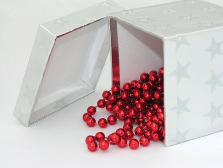 A silver gift box with red christmas beads hanging out. Stock Photo