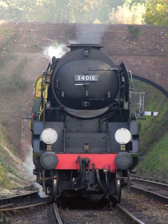 A steam train going under a bridge