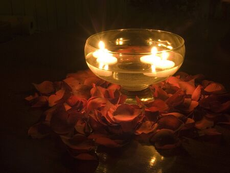 Floating candles in a glass bowl of water with rose petals around the outside.
