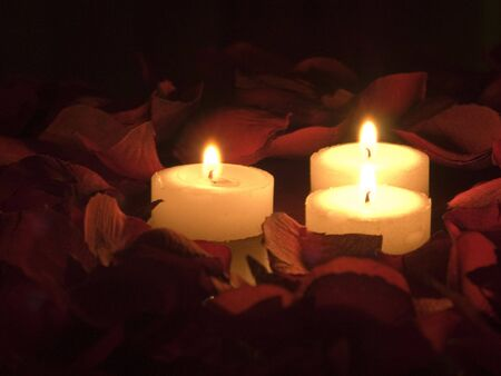 Three burning candles surrounded by rose petals