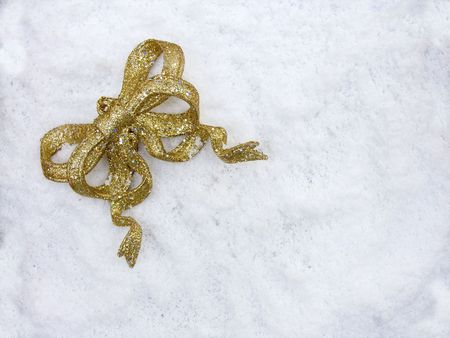 A gold glittery christmas deocration ribbon on snow
