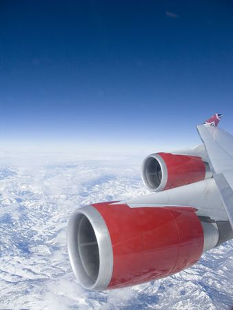 View from an aeroplane window of the red engines over some mountains with a deep blue sky. Stock Photo