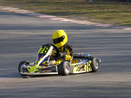 A racing yellow and black cadet go kart.