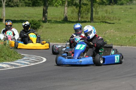 Some go karts racing on a corner Stock Photo