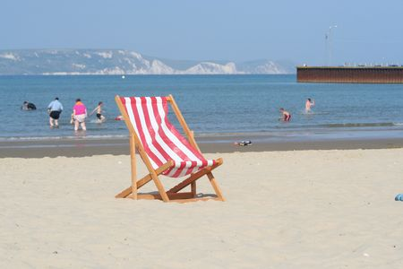 A stripey deckchair on a sandy beach