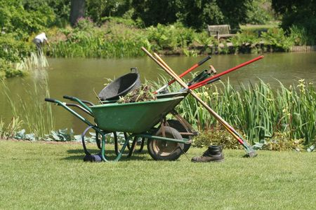 A variety of gardening tools with a pond in the background Stock Photo