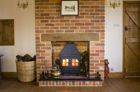 A lit wood burning stove in a farmhouse lounge