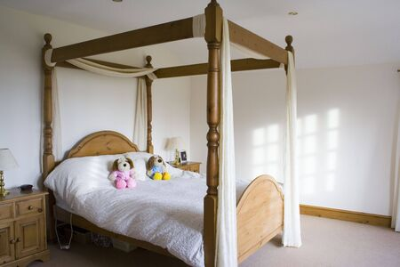 four poster bed: A four poster bed in a white bedroom