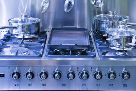 A new gas hob tinted blue with saucepans Stock Photo