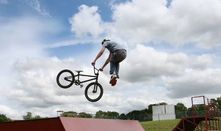 A stunt rider doing high jumps on a bmx bicycle