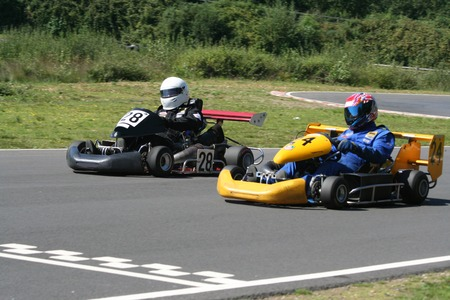 Two go karts racing across the finish line.