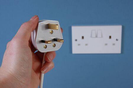 enchufe: Una mano izquierda sosteniendo un tap�n de pin de estilo 3 UK con un socket doble en una pared azul en el fondo.