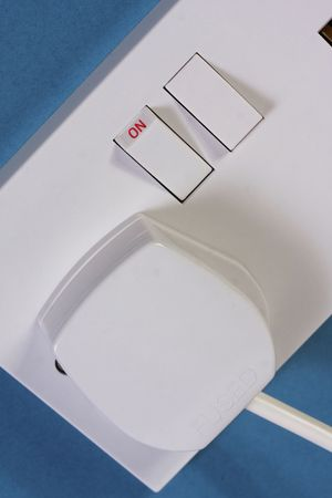 Close up of a UK style 3 pin plug in a double socket on a blue wall. Taken in vertical format photo