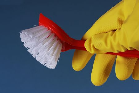 scrubbing up: Closeup of a yellow rubber glove holding a red washing up brush against a blue background.