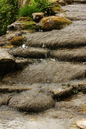 Vertical shot of water cascading down some shallow steps. photo