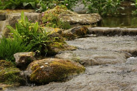 Water gently cascading down some shallow stones. photo