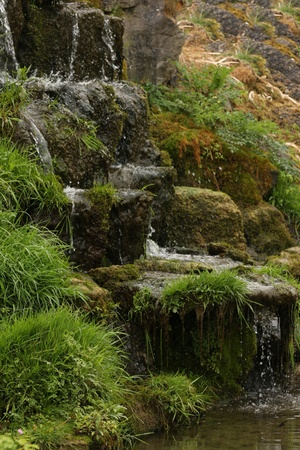 Vertical shot of water cascading down some a steep stony bank. photo