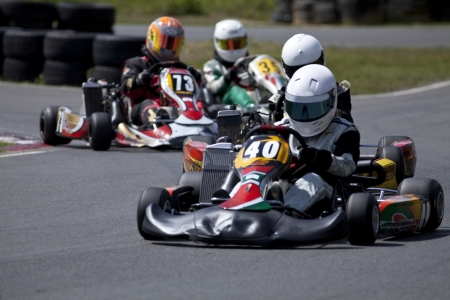 kart: Four adult racing go-karts coming out of a bend.