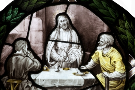 Stained glass window picture showing Jesus sharing bread and wine with two other men, similiar to the Last Supper.