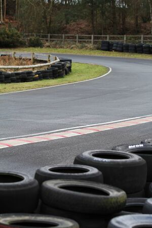 kerb: The bend of a race track taken in vertical format.  Image shows tyre barrier, tarmac, track, kerb and fencing.