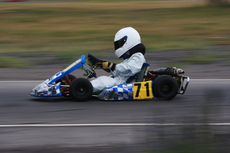 go kart: A panning technique shot of a speeding blue and silver cadet go kart with number 71 on the side pod.