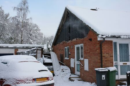 Snow damage to a house, the weight of the snow has collapsed the car port onto a parked car.