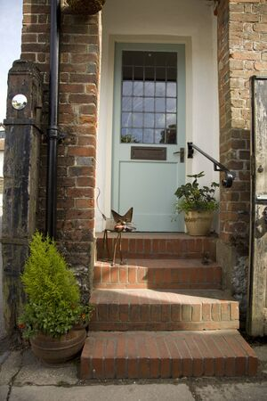 Old traditional door step taken in Selborne, Hampshire, England. Has a blue front door with steps.