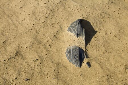 disappeared: A piece of abandoned car tyre whic has disappeared into the sand.