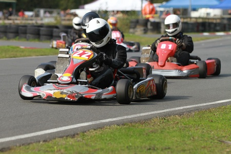 Adult racing go karts on a track coming out of a bend.