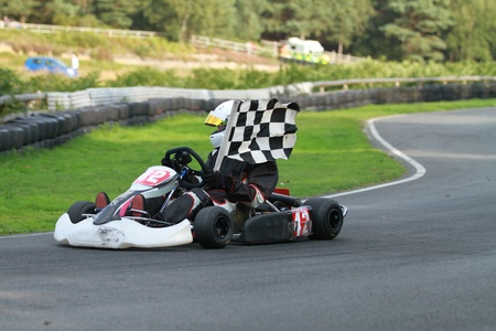 The winner of a go kart race on his parade lap of honour with the chequered flag.