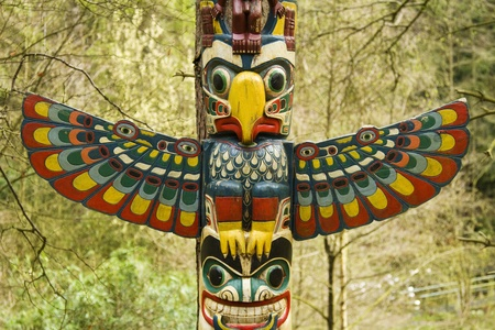 Section of a totem pole, a wooden structure featuring a bird with wings out. Stock Photo