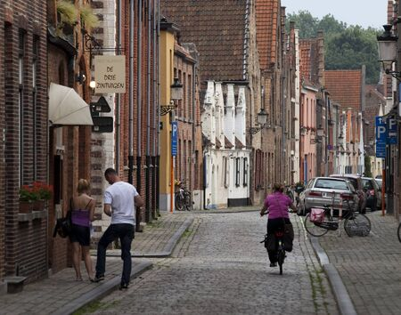 terraced: Typical cobbled street in Brugges, Belgium. Editorial picture with a couple and a lady on a bicycle.