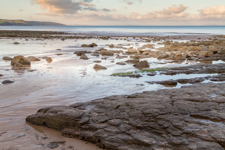 Evening at Saundersfoot beach in Pembrokeshire, Wales.  The tide is out revealing the rocky shore.