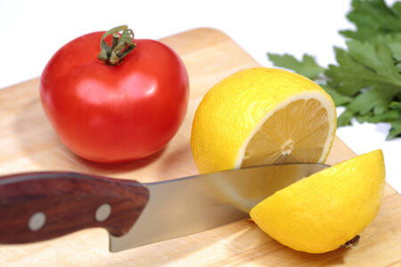 metal knife cuts the lemon and herbs, board, tomato photo