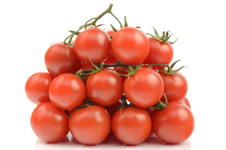 Fresh tomatoes with tails on a white background