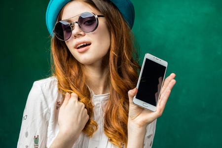Woman shows smartphone with smiling face and open mouth.Teenager demonstrate mobile phone in hand Stock Photo