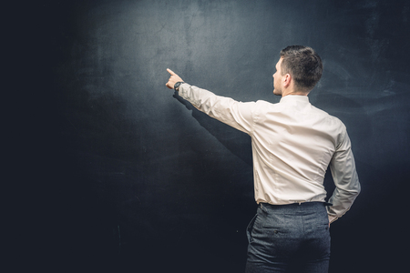 Man in suit pointing something on chalkboard,back view,isolated.Copyspace blank Stock Photo