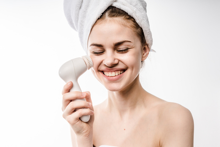 Enjoying charming woman with special brush for deep cleansing facial remove makeup. Skincare concept. High technology beauty. 스톡 콘텐츠