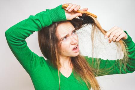 calvicie: Girl combs hair isolated, hair loss, baldness. Lost hairs