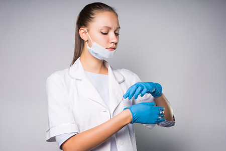 Een schattig meisje arts draagt een masker op haar gezicht, handschoenen aantrekken. Nadenkend vrouw naar beneden te kijken