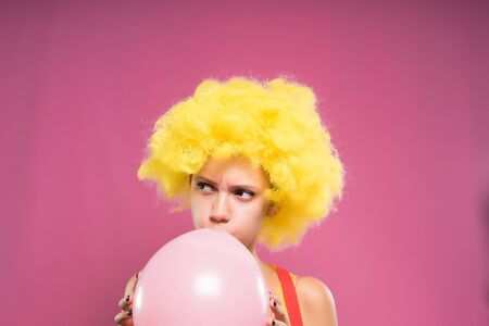 A clown girl in a yellow wig inflates a pink balloon. Isolated on a pink background