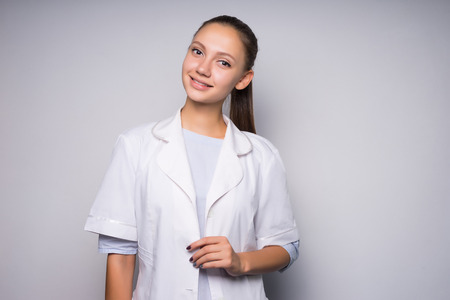 Young woman in white coat, looking at camera, smiling. Isolated on a gray background