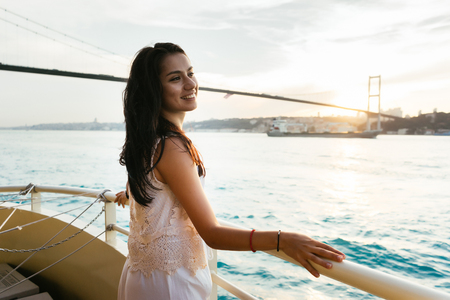 Young girl traveler relaxes while cruising on a yacht, looking at sunset, modern famous bridge on background